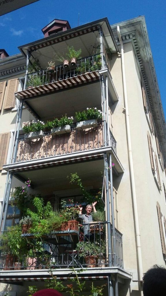 a lady in balcony greeting passerby